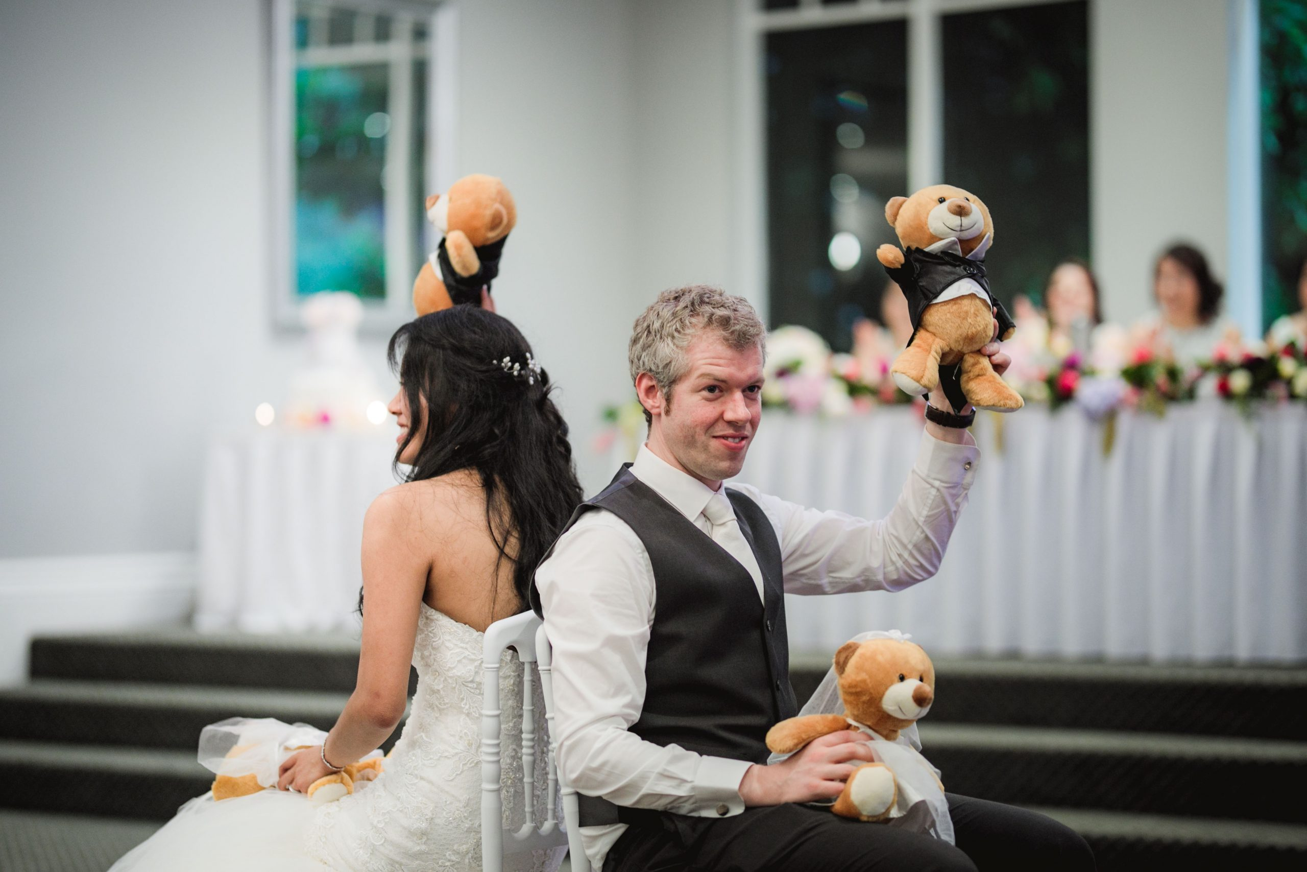 Bride and groom sitting back to back holding teddy bears
