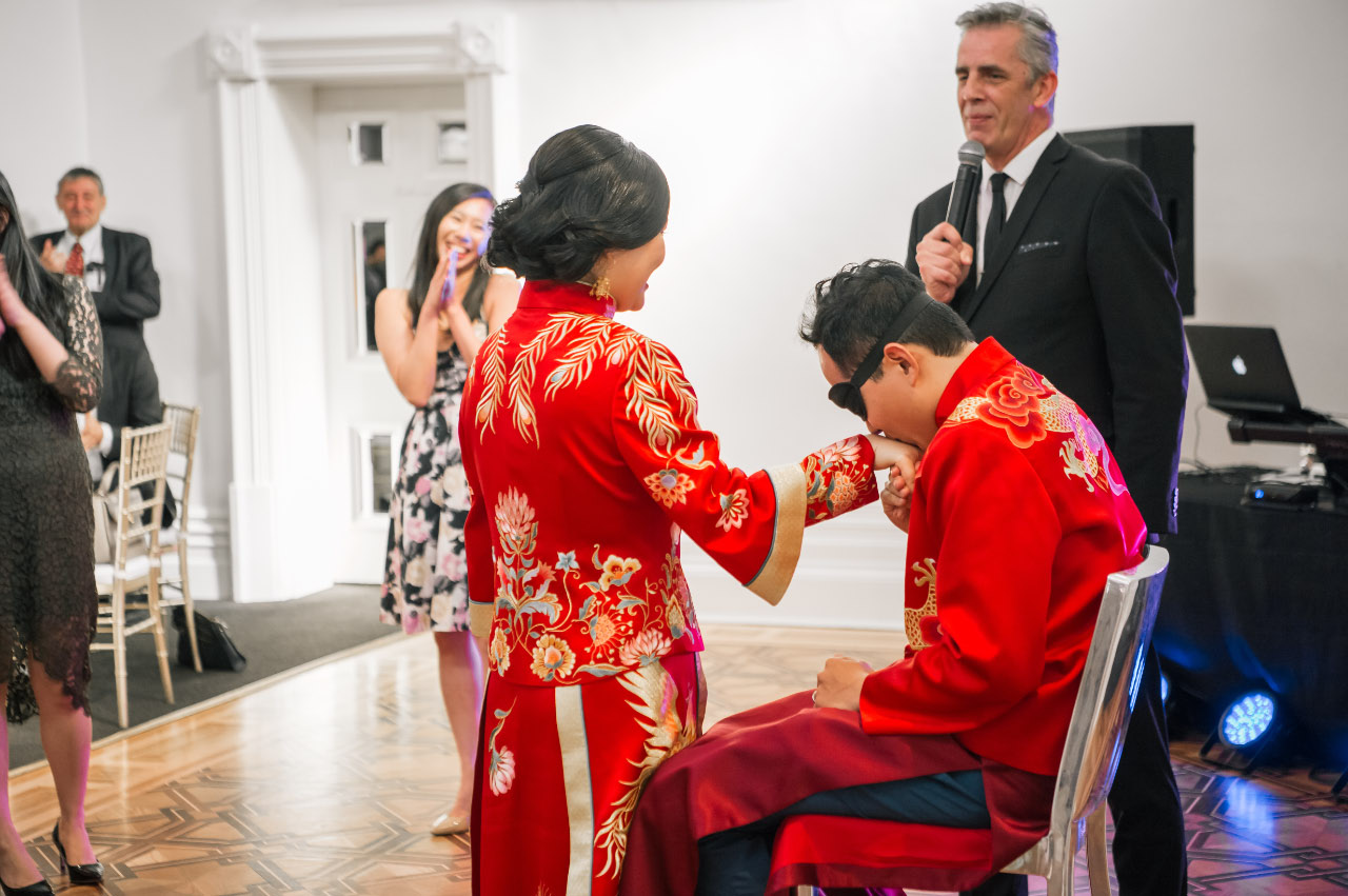 Bride and groom wearing red with Bruce Harrison talking