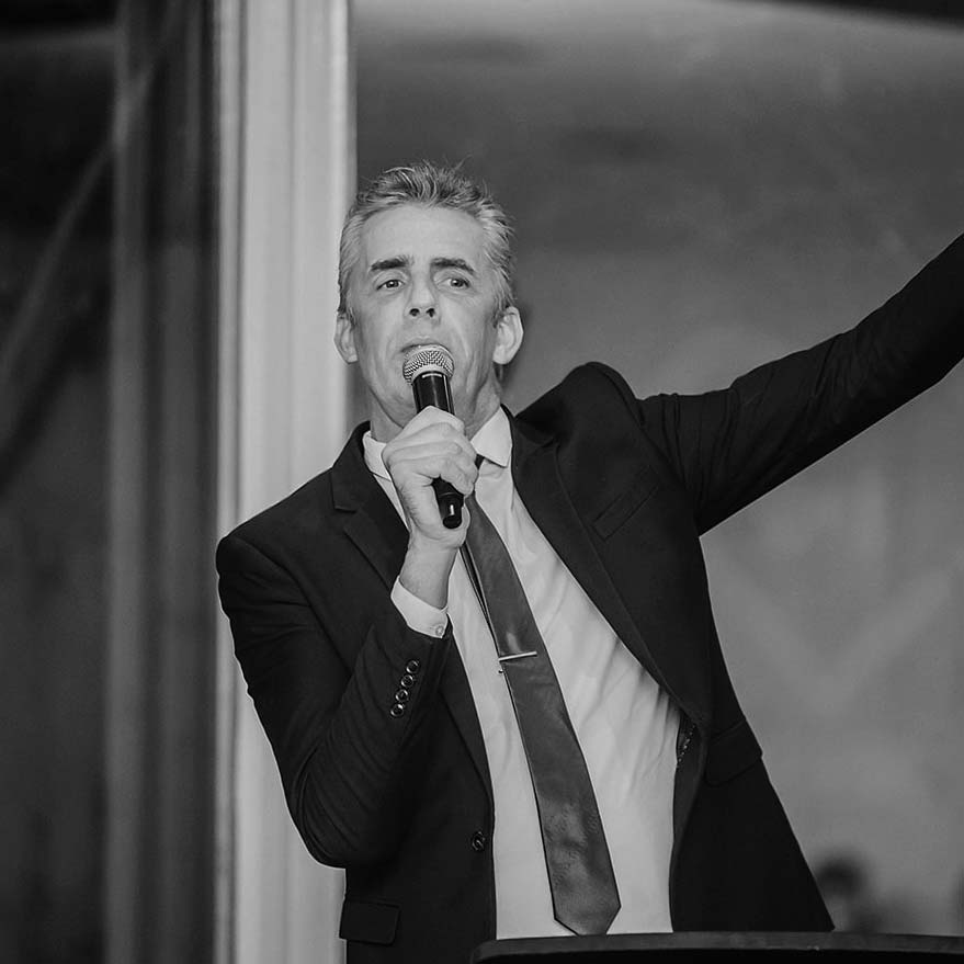 Black and white photo of Bruce Harrison speaking into a microphone